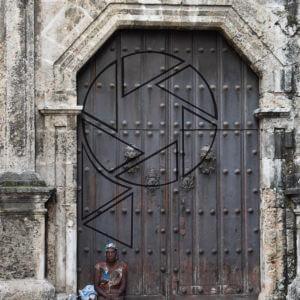 Smutná žena s dělem před kostelem